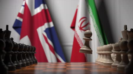satranç tahtası : Flags of the UK and Iran behind pawns on the chessboard. Chess game or political rivalry related 3D animation