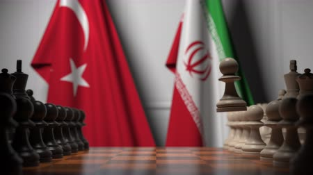 turk : Flags of Turkey and Iran behind pawns on the chessboard. Chess game or political rivalry related 3D animation