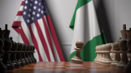 nigeria flag : Flags of USA and Nigeria behind pawns on the chessboard. Chess game or political rivalry related 3D animation Stock Footage
