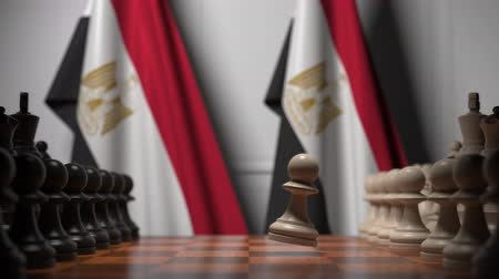 šachy : Flags of Egypt behind pawns on the chessboard. Chess game or political rivalry related 3D animation