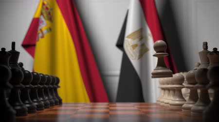 spaniard : Flags of Spain and Egypt behind pawns on the chessboard. Chess game or political rivalry related 3D animation Stock Footage