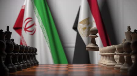 Иран : Flags of Iran and Egypt behind pawns on the chessboard. Chess game or political rivalry related 3D animation Стоковые видеозаписи