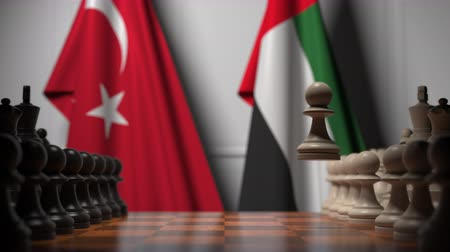 turk : Flags of Turkey and UAE behind pawns on the chessboard. Chess game or political rivalry related 3D animation