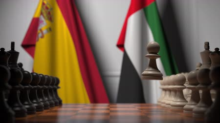spaniard : Flags of Spain and UAE behind pawns on the chessboard. Chess game or political rivalry related 3D animation