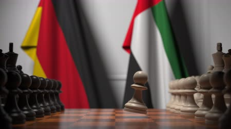 соперничество : Flags of Germany and UAE behind pawns on the chessboard. Chess game or political rivalry related 3D animation Стоковые видеозаписи