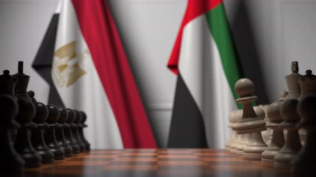 xadrez : Flags of Egypt and UAE behind pawns on the chessboard. Chess game or political rivalry related 3D animation