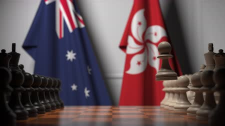šachy : Flags of Australia and Hong Kong behind pawns on the chessboard. Chess game or political rivalry related 3D animation