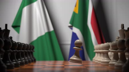 nigeria flag : Flags of Nigeria and South Africa behind pawns on the chessboard. Chess game or political rivalry related 3D animation