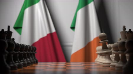 drapeau irlandais : Flags of Italy and Ireland behind pawns on the chessboard. Chess game or political rivalry related 3D animation