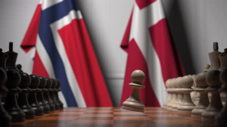 danish : Flags of Norway and Denmark behind pawns on the chessboard. Chess game or political rivalry related 3D animation Stock Footage