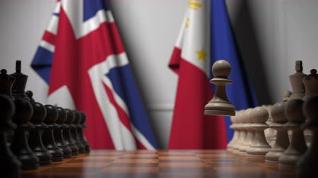 конкурировать : Flags of Great Britain and Philippines behind pawns on the chessboard. Chess game or political rivalry related 3D animation