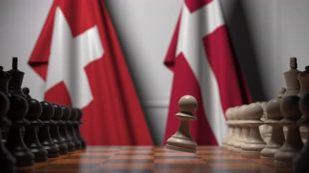 конкурировать : Flags of Switzerland and Denmark behind pawns on the chessboard. Chess game or political rivalry related 3D animation