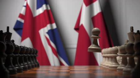 deense dog : Flags of the United Kingdom and Denmark behind pawns on the chessboard. Chess game or political rivalry related 3D animation