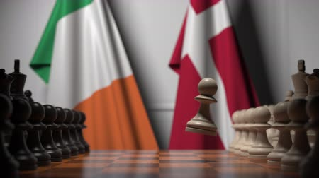 danimarka : Flags of Republic of Ireland and Denmark behind pawns on the chessboard. Chess game or political rivalry related 3D animation Stok Video