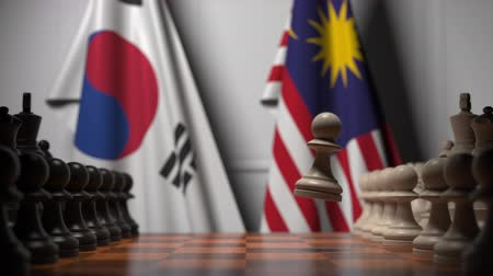 概念 : Flags of South Korea and Malaysia behind pawns on the chessboard. Chess game or political rivalry related 3D animation 影像素材