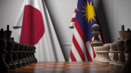 tablero de ajedrez : Flags of Japan and Malaysia behind pawns on the chessboard. Chess game or political rivalry related 3D animation Archivo de Video