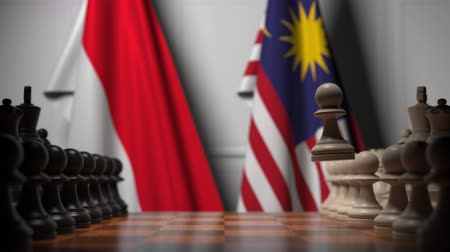 tabuleiro de xadrez : Flags of Indonesia and Malaysia behind pawns on the chessboard. Chess game or political rivalry related 3D animation Stock Footage