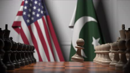 paquistão : Flags of USA and Pakistan behind pawns on the chessboard. Chess game or political rivalry related 3D animation Stock Footage