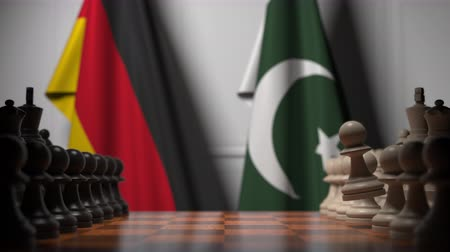 šachy : Flags of Germany and Pakistan behind pawns on the chessboard. Chess game or political rivalry related 3D animation