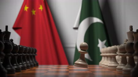 drapeau chine : Flags of China and Pakistan behind pawns on the chessboard. Chess game or political rivalry related 3D animation