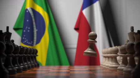 šachy : Flags of Brazil and Chile behind pawns on the chessboard. Chess game or political rivalry related 3D animation
