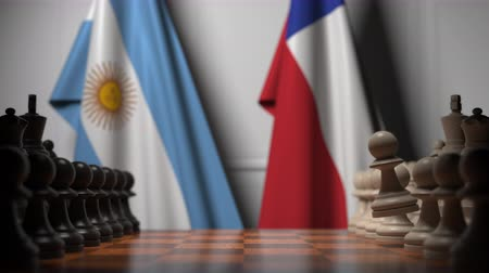 versengés : Flags of Argentina and Chile behind pawns on the chessboard. Chess game or political rivalry related 3D animation Stock mozgókép
