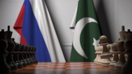 tabuleiro de xadrez : Flags of Russia and Pakistan behind pawns on the chessboard. Chess game or political rivalry related 3D animation