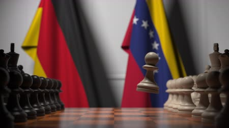 šachy : Flags of Germany and Venezuela behind pawns on the chessboard. Chess game or political rivalry related 3D animation