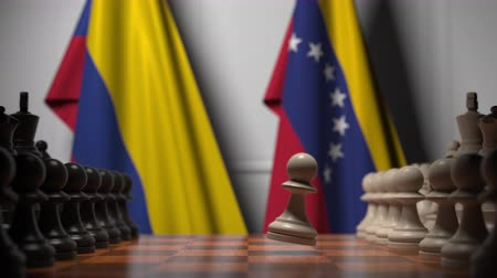 соперничество : Flags of Colombia and Venezuela behind pawns on the chessboard. Chess game or political rivalry related 3D animation