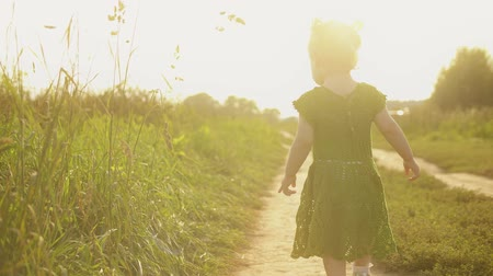 szandál : Baby girl wearing green dress walks along the path on a hot sunny summer evening