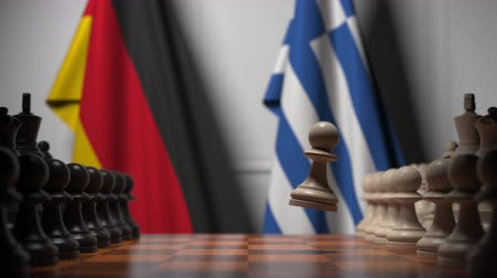 versengés : Flags of Germany and Greece behind pawns on the chessboard. Chess game or political rivalry related 3D animation