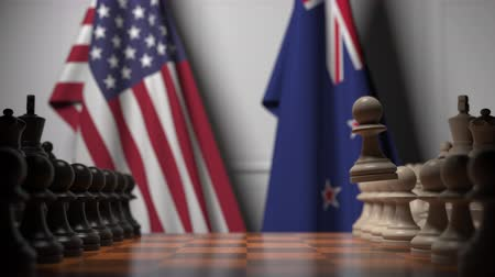 nowa zelandia : Flags of the USA and New Zealand behind pawns on the chessboard. Chess game or political rivalry related 3D animation