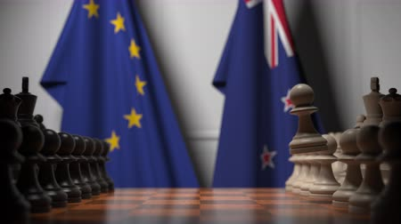 nowa zelandia : Flags of the European Union EU and New Zealand behind pawns on the chessboard. Chess game or political rivalry related 3D animation