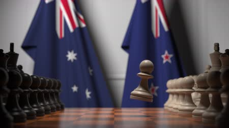 nowa zelandia : Flags of Australia and New Zealand behind pawns on the chessboard. Chess game or political rivalry related 3D animation