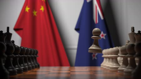 versengés : Flags of China and New Zealand behind pawns on the chessboard. Chess game or political rivalry related 3D animation Stock mozgókép
