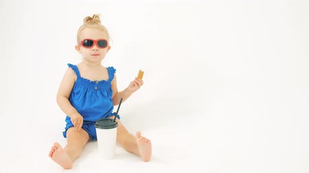 sede : Portrait of a baby girl wearing sunglasses and blue dress having snack on white background