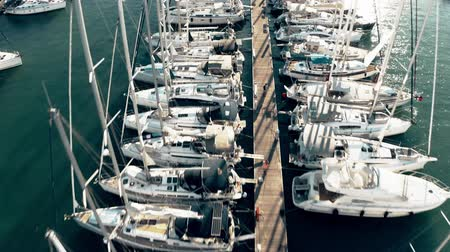 docked : Low altitude aerial down view of a marina pier and many docked sailing yachts