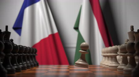 соперничество : Flags of France and Hungary behind pawns on the chessboard. Chess game or political rivalry related 3D animation
