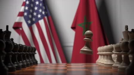 šachy : Flags of USA and Morocco behind pawns on the chessboard. Chess game or political rivalry related 3D animation