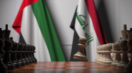 irak : Flags of the United Arab Emirates and Iraq behind pawns on the chessboard. Chess game or political rivalry related 3D animation