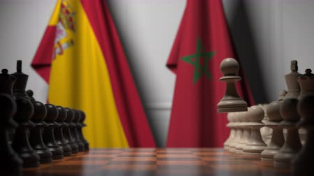 autoridade : Flags of Spain and Morocco behind pawns on the chessboard. Chess game or political rivalry related 3D animation
