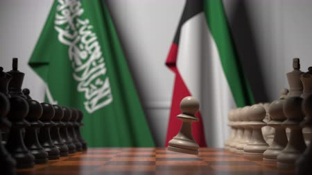 autoridade : Flags of Saudi Arabia and Kuwait behind pawns on the chessboard. Chess game or political rivalry related 3D animation