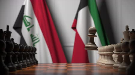 irak : Flags of Iraq and Kuwait behind pawns on the chessboard. Chess game or political rivalry related 3D animation Stockvideo