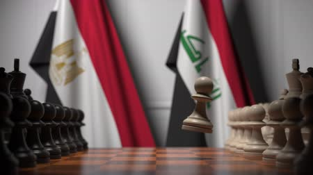 irak : Flags of Egypt and Iraq behind pawns on the chessboard. Chess game or political rivalry related 3D animation