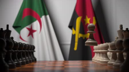 algeria : Flags of Algeria and Angola behind pawns on the chessboard. Chess game or political rivalry related 3D animation Stock Footage