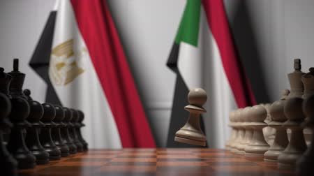 sudanian : Flags of Egypt and Sudan behind pawns on the chessboard. Chess game or political rivalry related 3D animation Stock Footage