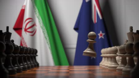 nowa zelandia : Flags of Iran and New Zealand behind pawns on the chessboard. Chess game or political rivalry related 3D animation