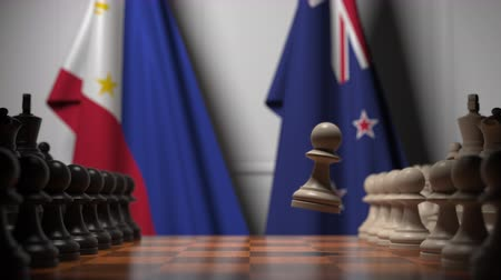 nowa zelandia : Flags of Philippines and New Zealand behind pawns on the chessboard. Chess game or political rivalry related 3D animation