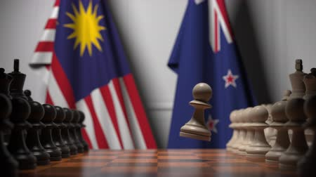 nouvelle zélande : Flags of Malaysia and New Zealand behind pawns on the chessboard. Chess game or political rivalry related 3D animation