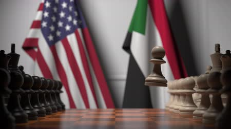 sudanian : Flags of USA and Sudan behind pawns on the chessboard. Chess game or political rivalry related 3D animation